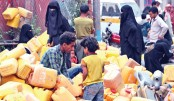 Yemenis gather with plastic containers as they wait to collect water from a tank