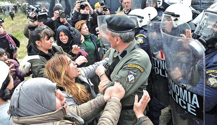 Women clashes with Greek riot police as migrants gather outside of a refugee camp