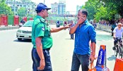 A policeman intercepts a pedestrian for crossing a busy road using earphones