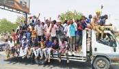 Sudanese men celebrate on Thursday while rallying in capital Khartoum
