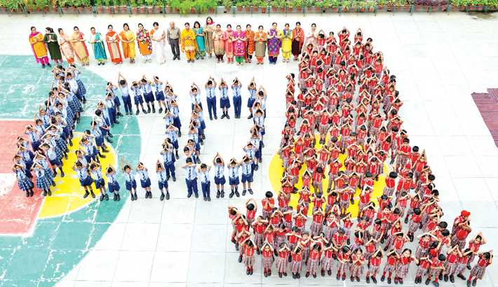Indian school students and teachers stand in the shape of the number '100'