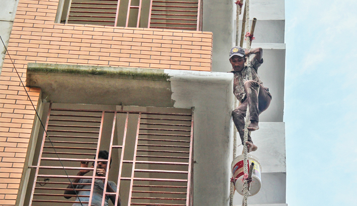 Worker is painting a building without minimum safety measures