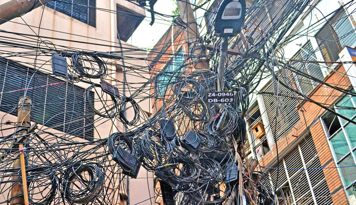 Electric poles entangled with internet, TV cables