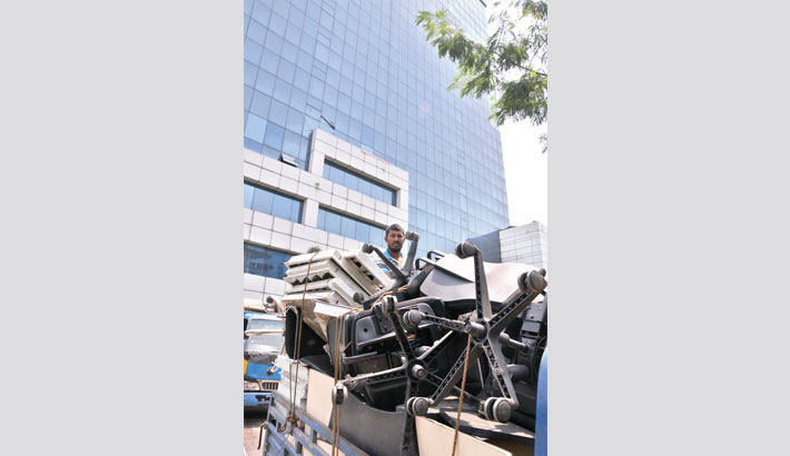 A pick-up van loaded with goods leaves the 15-storey BGMEA headquarters
