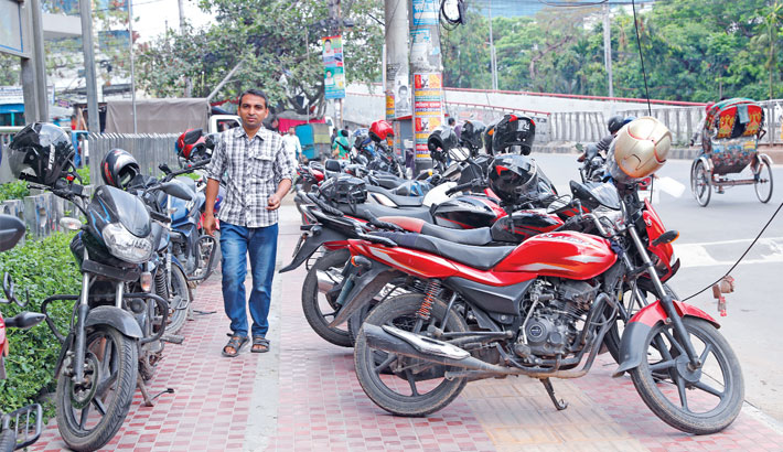A passer-by walks through motorbikes parked illegally on a footpath