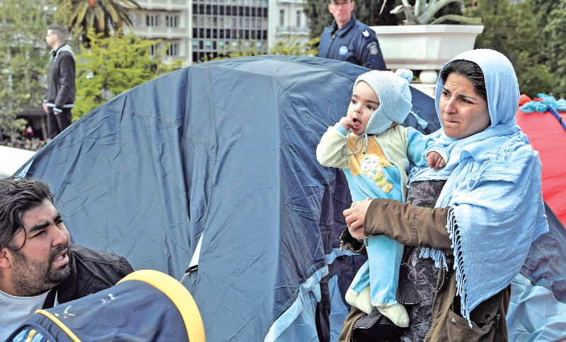 A migrant mother stands by a tent as a group of migrants and refugees camped