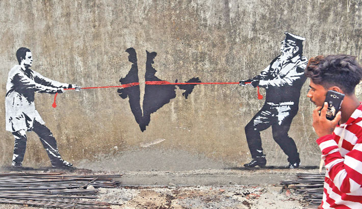 An Indian man speaks on his mobile phone as he walks past a wall graffiti