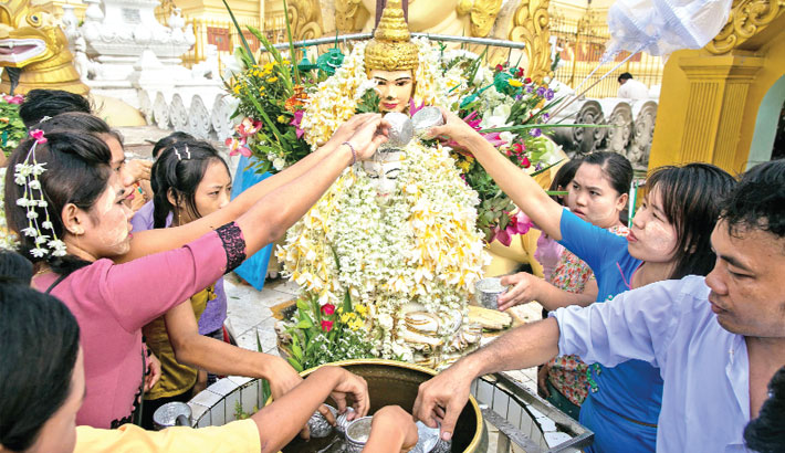Buddhist devotees pour water