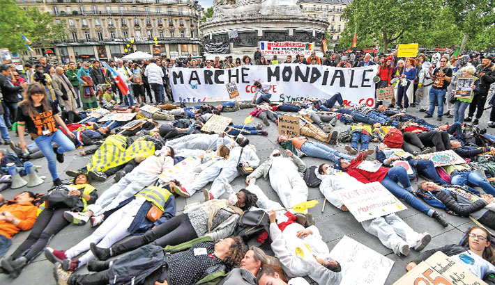 "People lie on the ground to stage an action called ""die-in"" as they gather"