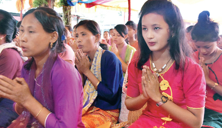 Women attend a mass prayer at a Buddha monastery