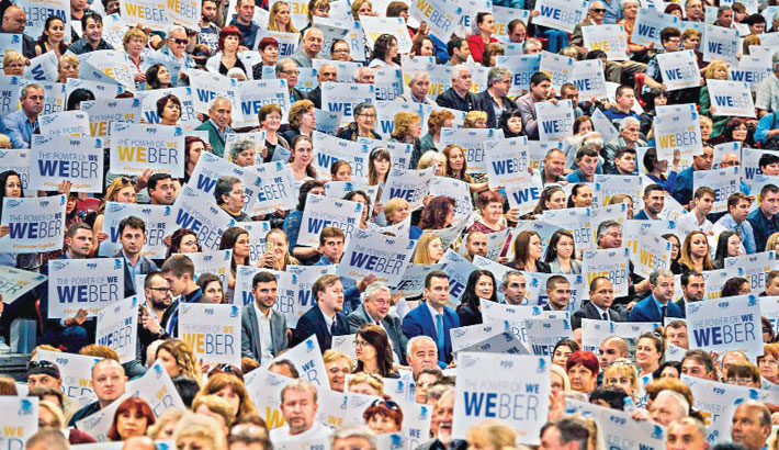 People hold posters to support Manfred Weber of the European People's Party