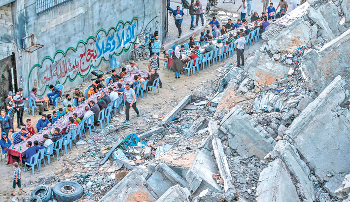 Palestinian families break their fast next to a destroyed building during recent confrontation between Hamas and Israel