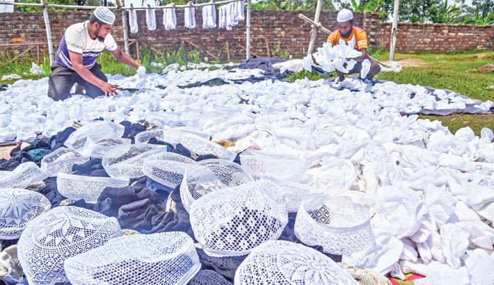 Two workers are drying prayer caps
