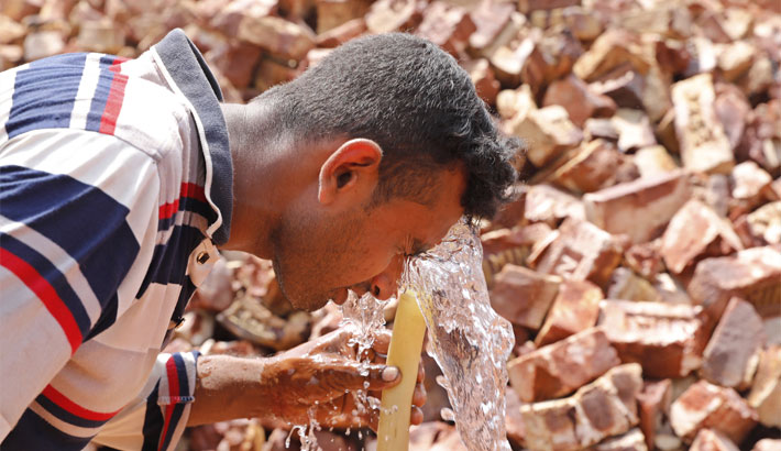 A day labourer takes a splash of water