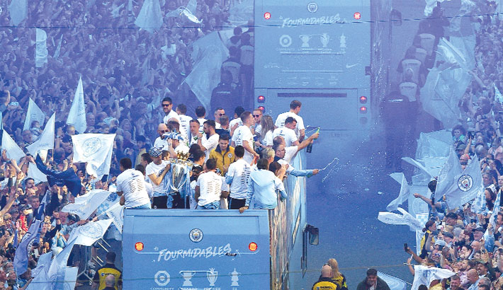 Fans line the streets as Manchester City football team take part