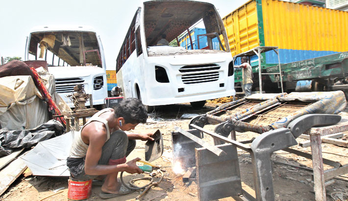 Worker remains busy welding at a motor vehicle workshop