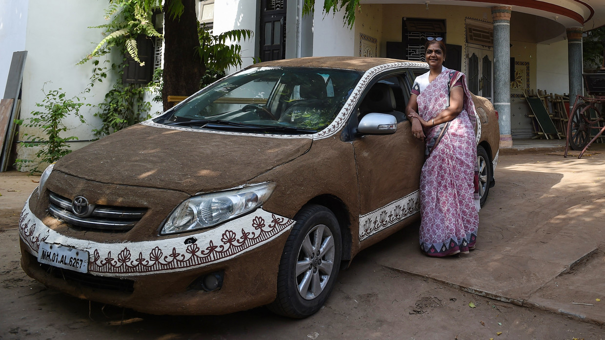 Indian woman coats car with cow dung, claims it cools without AC
