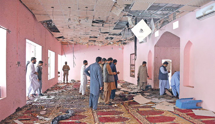 Pakistani security officials examine the interior of a mosque after a blast