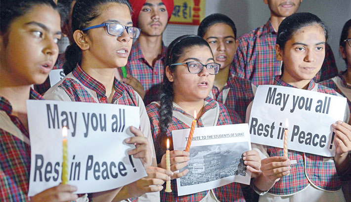Indian students hold candles