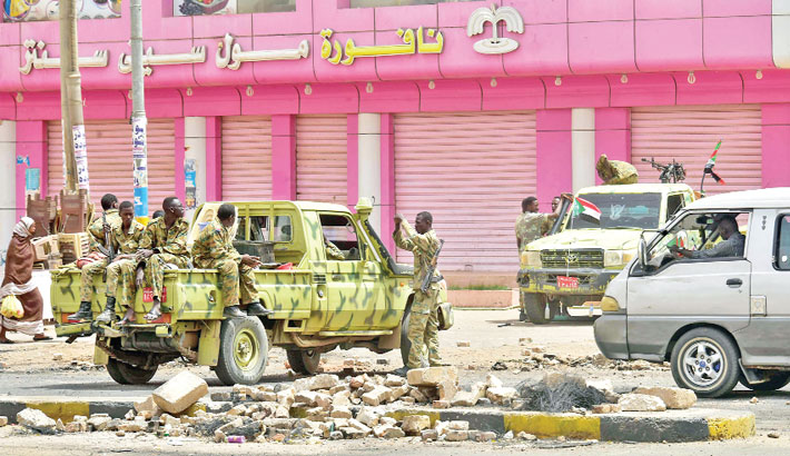 Sudanese soldiers stand guard a street