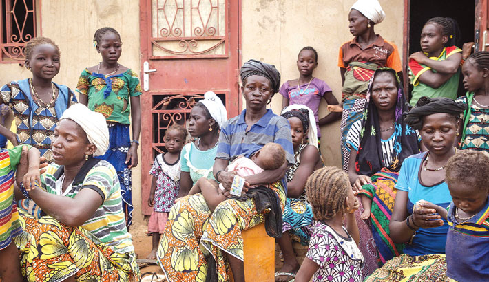 Women and children stand outside a school used as a shelter for Internally Displaced People (IDP)