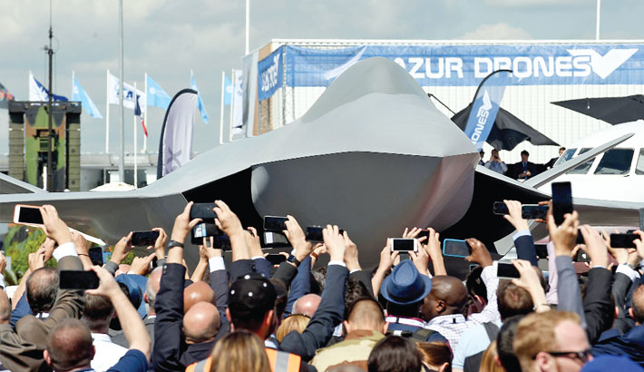Visitors watch the unveiling ceremony of the full-scale jet fighter model o