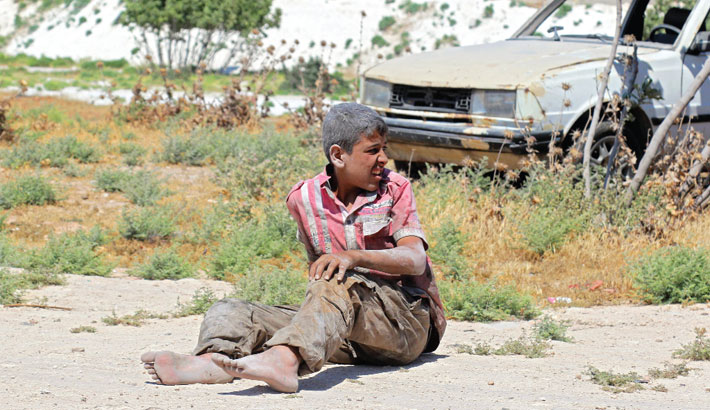 Young Syrian man sits on the ground after a bombing on an industrial area