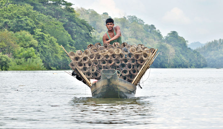 A fisherman returns home with fishing traps made of bamboo on his boat