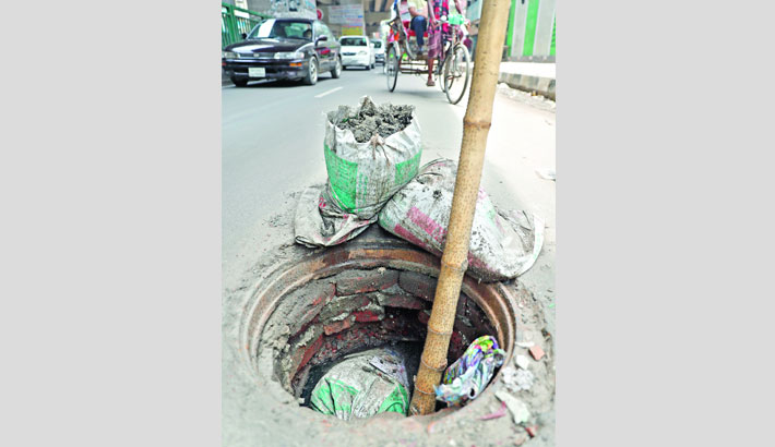 Manhole lies open on a busy road