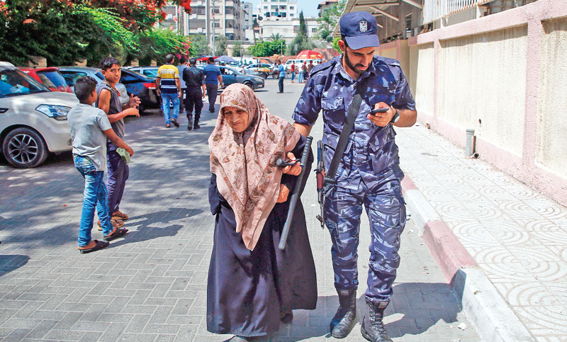 A member of the Palestinian security forces helps an old lady outside the post office in Gaza City
