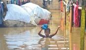 Indian boy wades through a flooded area
