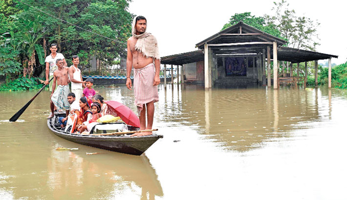 Indian villagers travel on a boat through flood waters