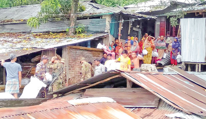 Bangladesh Army personnel distribute relief materials among flood-affected people