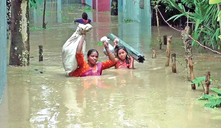 Flood-affected women wade through chest-deep water to go to a safe place