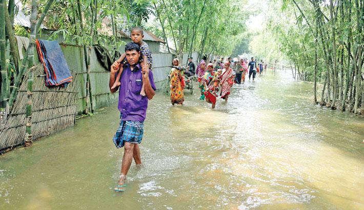 People wade through knee-deep water on a road
