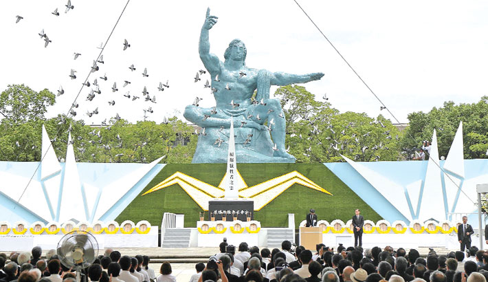 Doves fly around the Peace Statue
