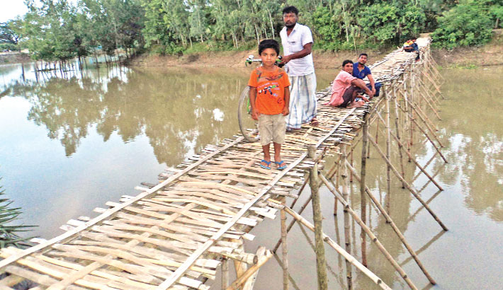 Local people use a risky bamboo bridge to cross the Nagor river