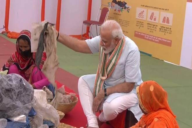 Modi picks plastic from waste along with garbage workers