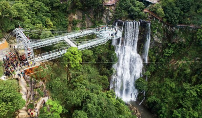Terrified tourists brave glass-bottomed bridge and its platform over cliff edge