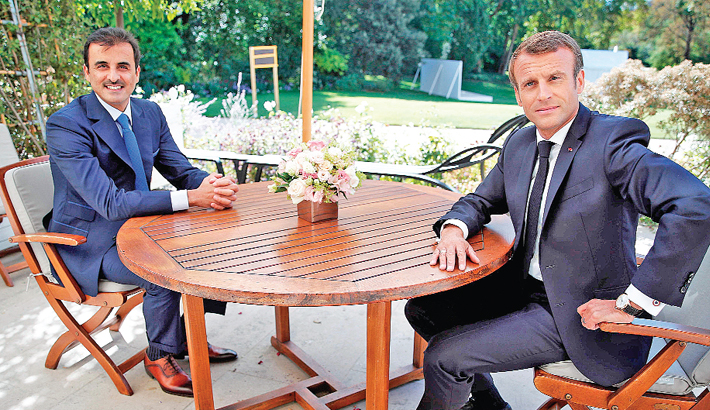 French president sits in front of the emir of Qatar