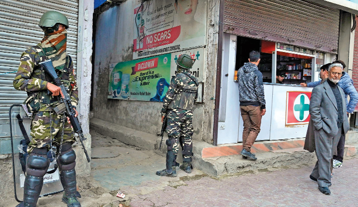 Indian paramilitary troopers stand guard