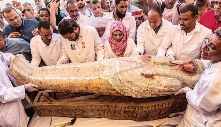 Egyptian archeologist open a wooden coffin