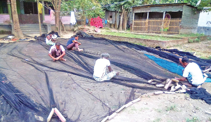 Fishermen are busy repairing fishing nets