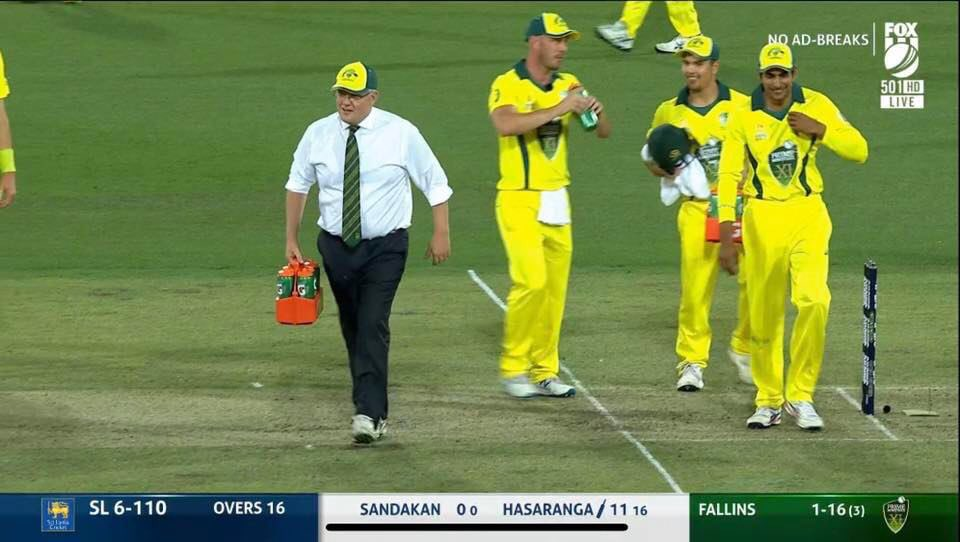 Australia PM Scott Morrison serves water to cricketers