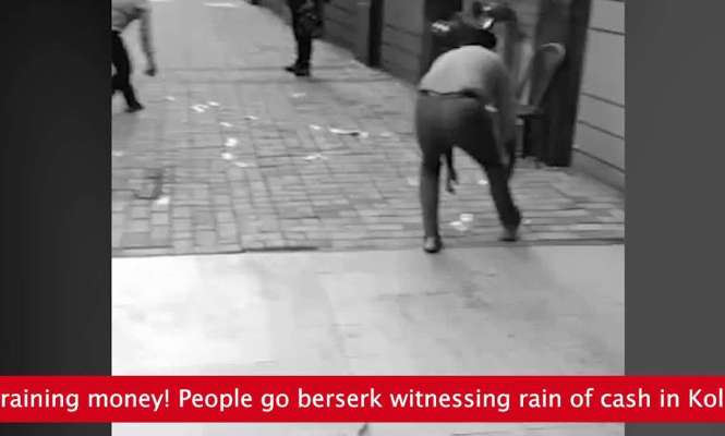 Bundles of cash rain down on street (Video)
