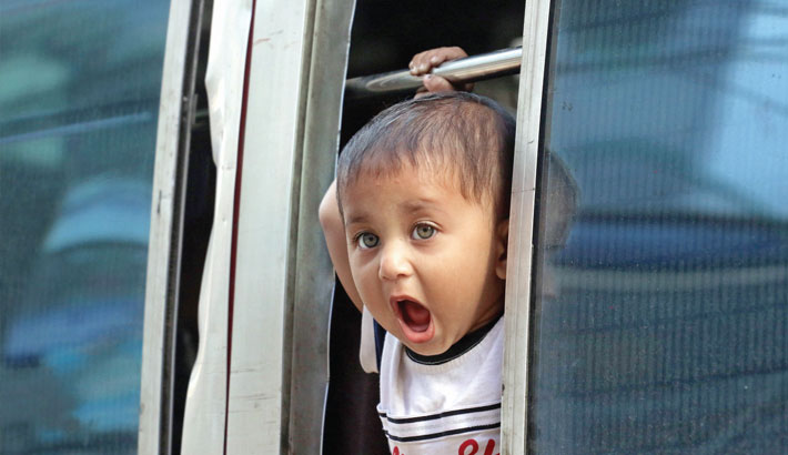 A toddler looks through the window of a running bus