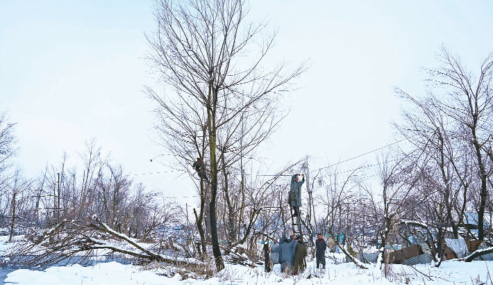 People repair electric wires after a heavy snowfall