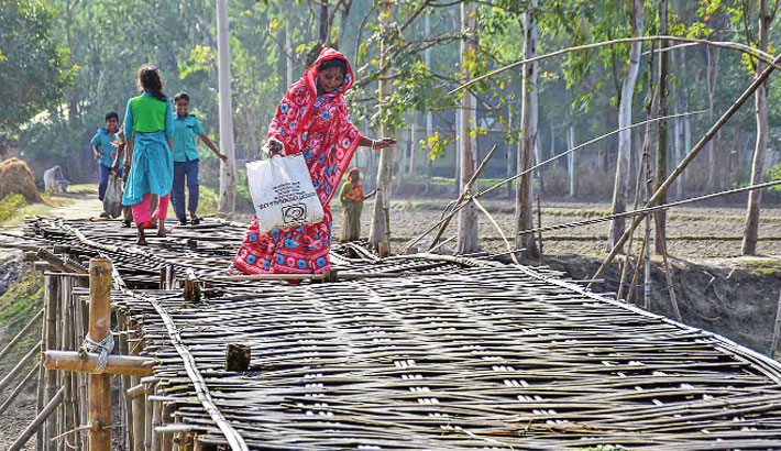 Local people use a risky bamboo bridge to cross the canal