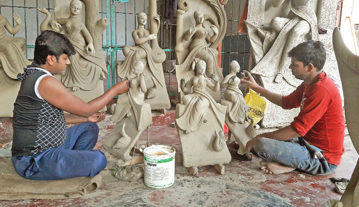 Artisans are seen busy making idols
