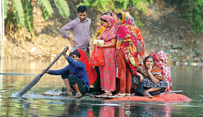 Residents of Korail slum in the capital cross a lake with murky water on corksheet-made raft